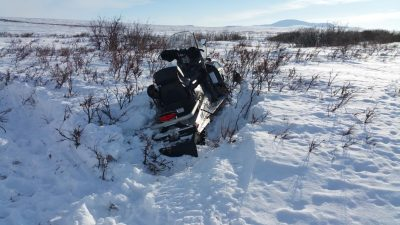 stuck snow machine in mixture of snow and tundra brush