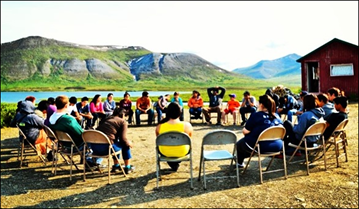 people sitting in folding chairs, outside in a large circle