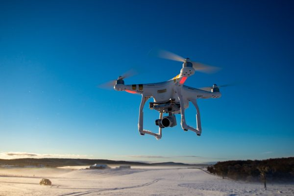 a drone flies over a snowy field with a vehicle in the background