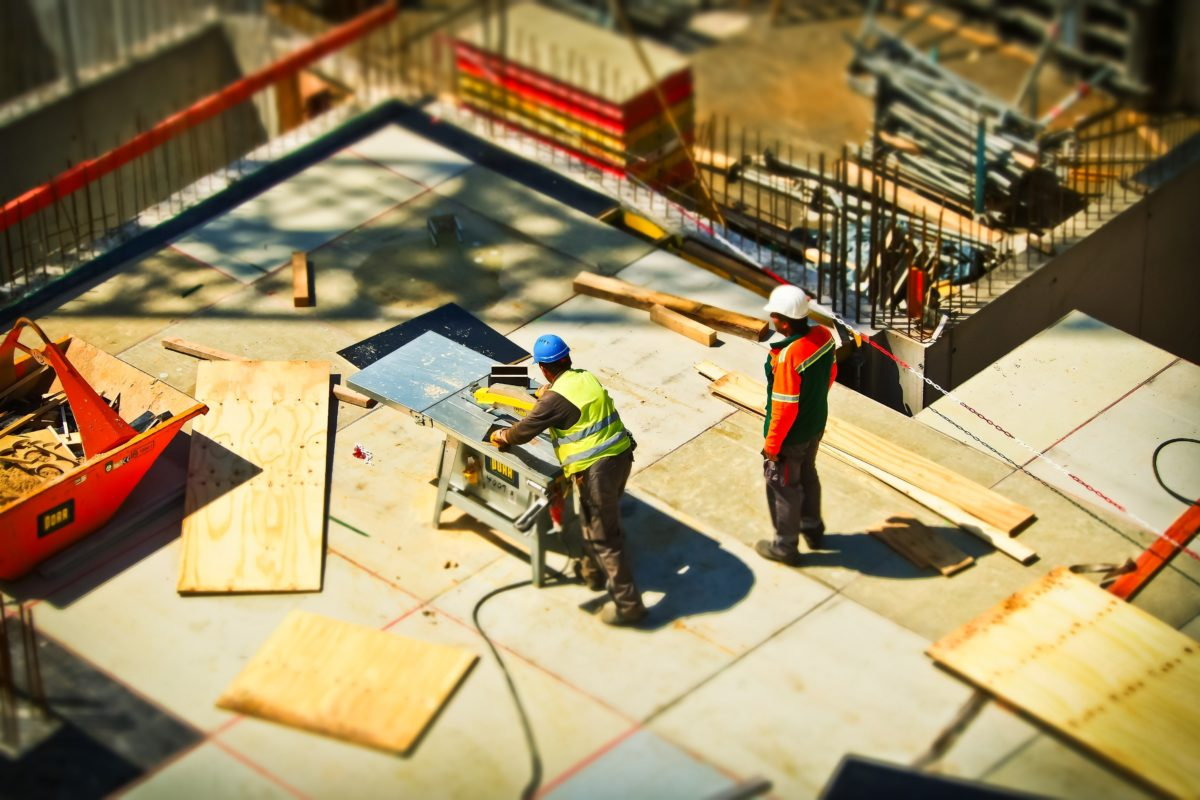 construction workers on a site with plywood and a table saw