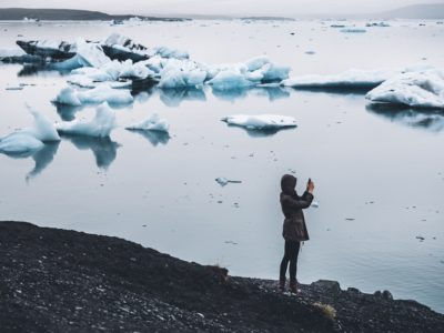 woman taking a picture along a beach with icebergs in the background