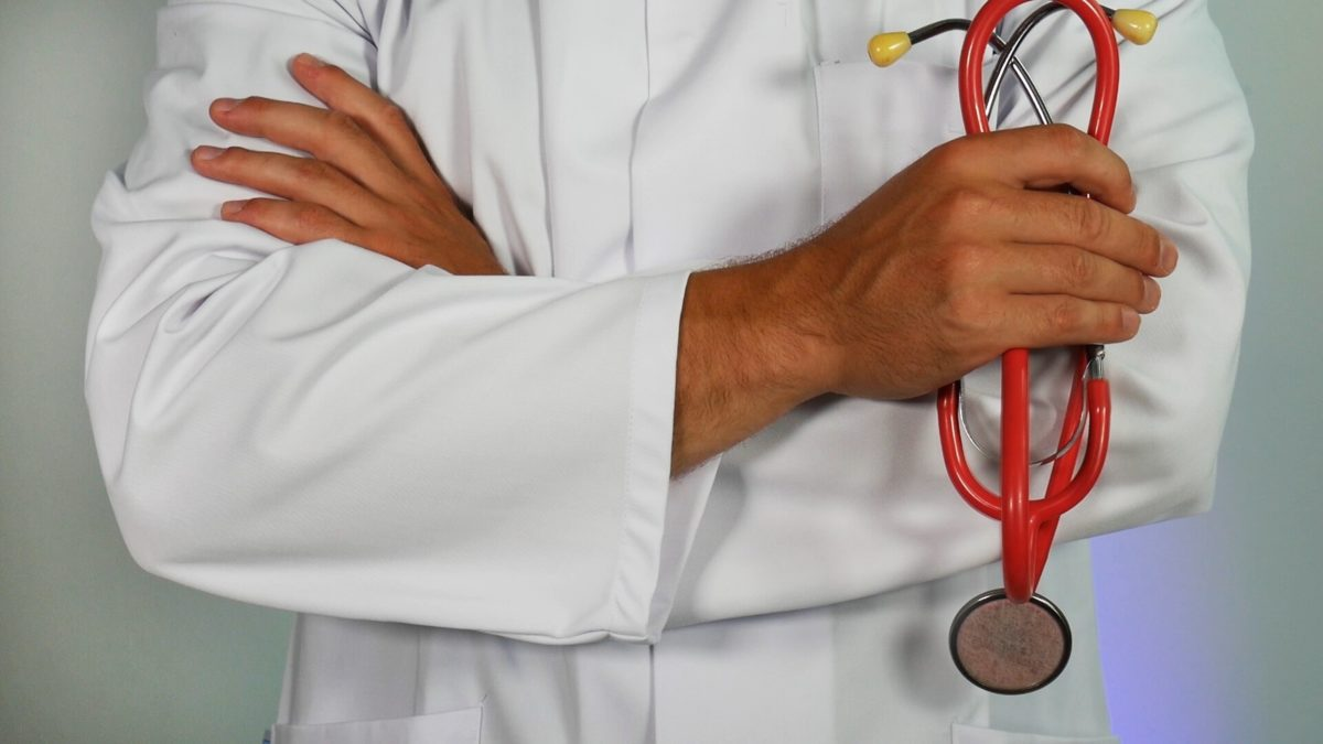 person in white coat holding stethoscope
