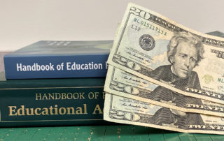 two books on education policy with three $20 bills