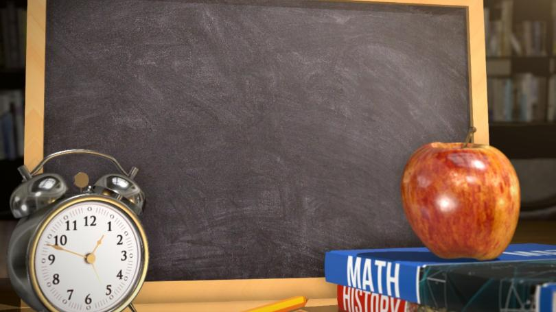 empty small chalkboard with 2 books, an apple, and an old style alarm clock