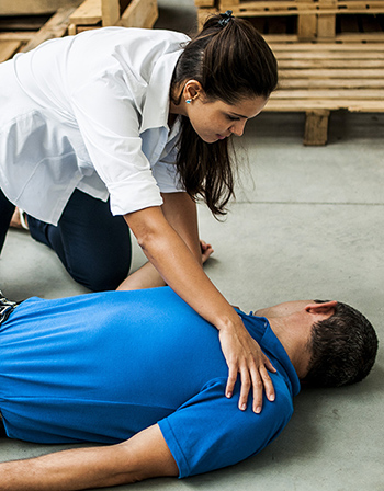 woman assisting an unconscious man after accident