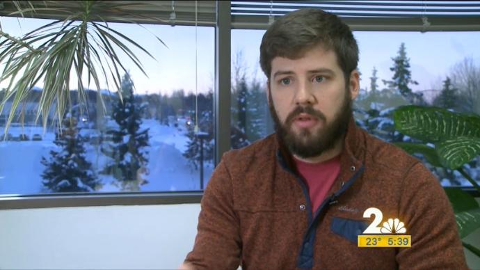 Kevin Berry being interviewed in front of two large windows looking at a snowy Anchorage Bragaw Street
