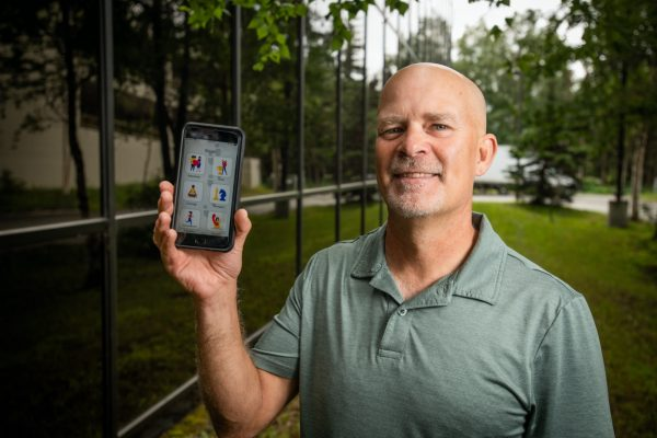 Professor Patrick Dulin holding a smart phone showing the Step Away app