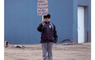 Front cover of UArctic's Magazine, Shared Voices 2020 featuring a kid holding a sign in front of a blue building